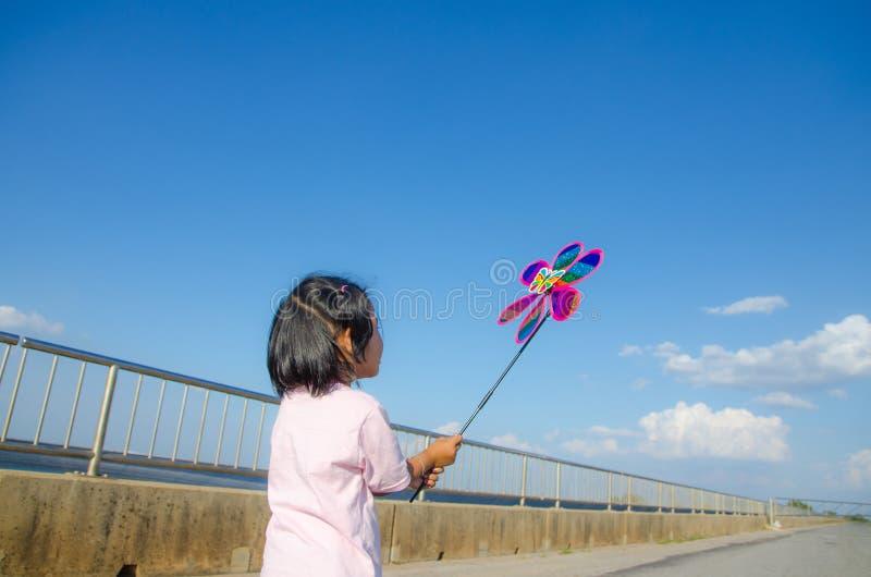 Niña asiática con el juguete de la turbina de viento en manos foto de archivo