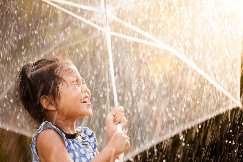 Niña asiática feliz con el paraguas en lluvia imagenes de archivo