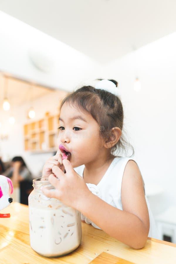 Niña asiática que bebe el cacao feliz feliz imagenes de archivo