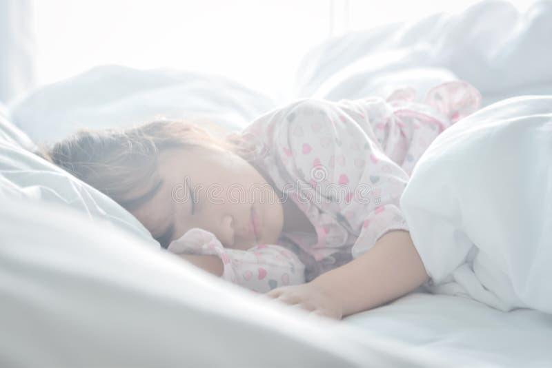 Niña asiática que duerme en la cama en el tiempo de mañana con concepto ideal dulce del foco suave ligero de la salida del sol foto de archivo libre de regalías