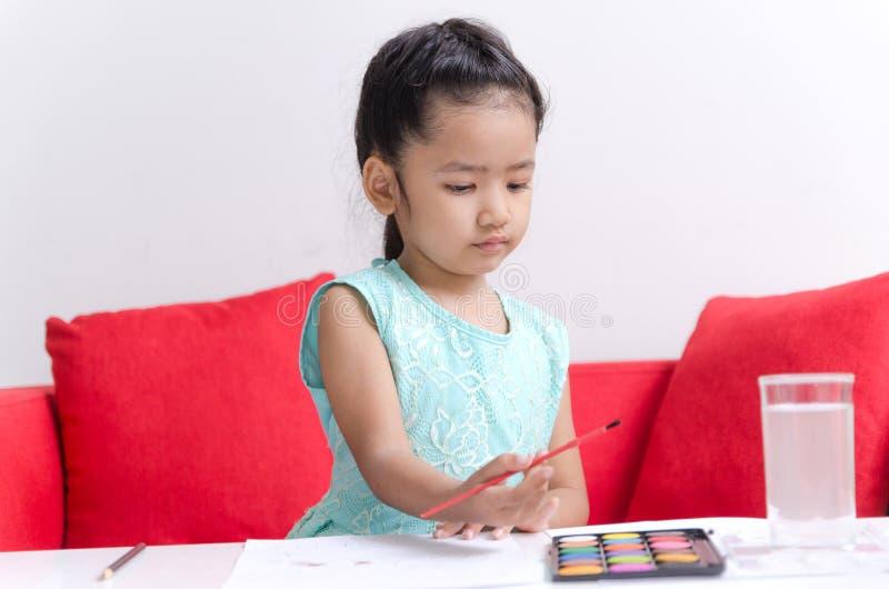 Niña asiática que juega jugando el color de agua, dibujando imagen de archivo libre de regalías