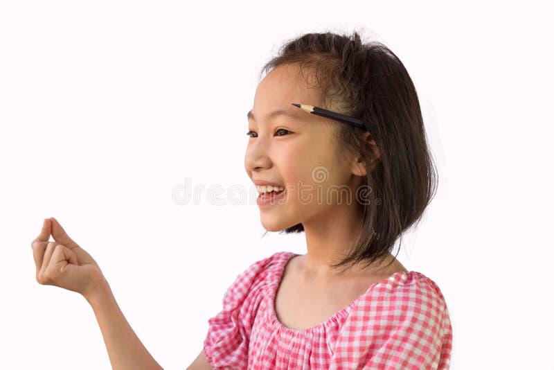 Niña asiática que piensa con un lápiz detrás de su oído, buenas ideas para el trabajo, creatividad, analítica, Niño aislado en bl imagenes de archivo
