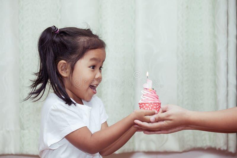 Niña asiática que se divierte a la magdalena del cumpleaños que sopla imagen de archivo