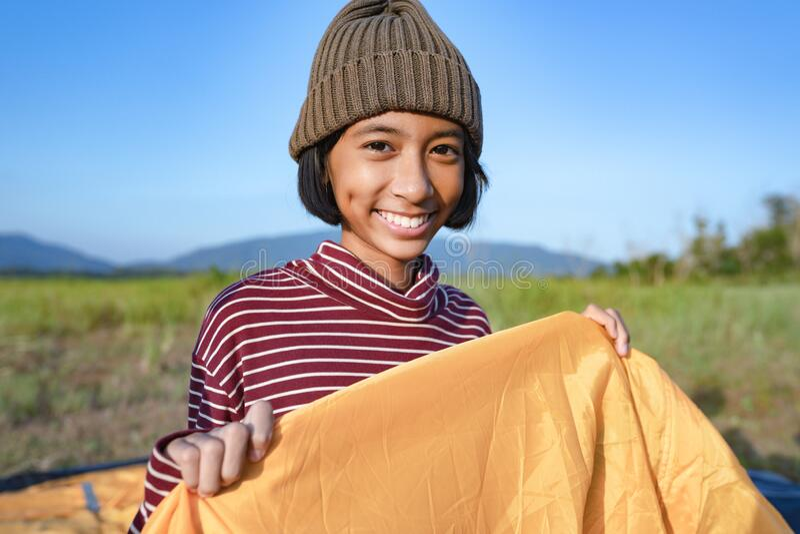 Niña asiática sonríe y disfruta la naturaleza en el camping en invierno El concepto de vida familiar durante las vacaciones fotografía de archivo
