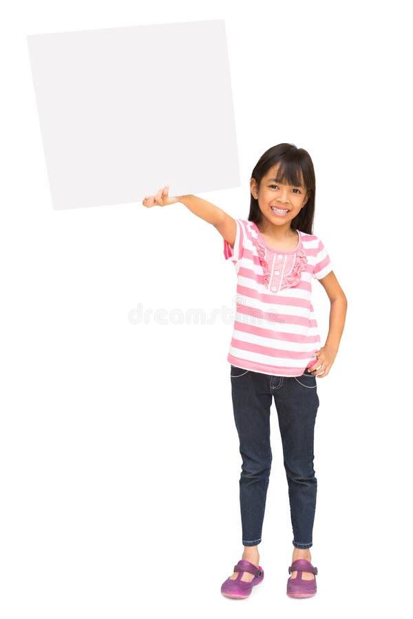 Niña asiática sonriente que lleva a cabo la muestra en blanco foto de archivo libre de regalías