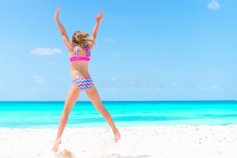 Niña asombrosa en la playa que se divierte mucho el vacaciones de verano Niño adorable que salta en la costa imágenes de archivo libres de regalías
