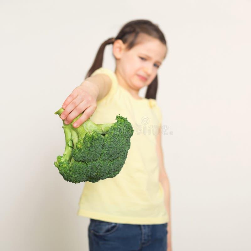 Niña asqueada con bróculi sobre el fondo blanco fotos de archivo