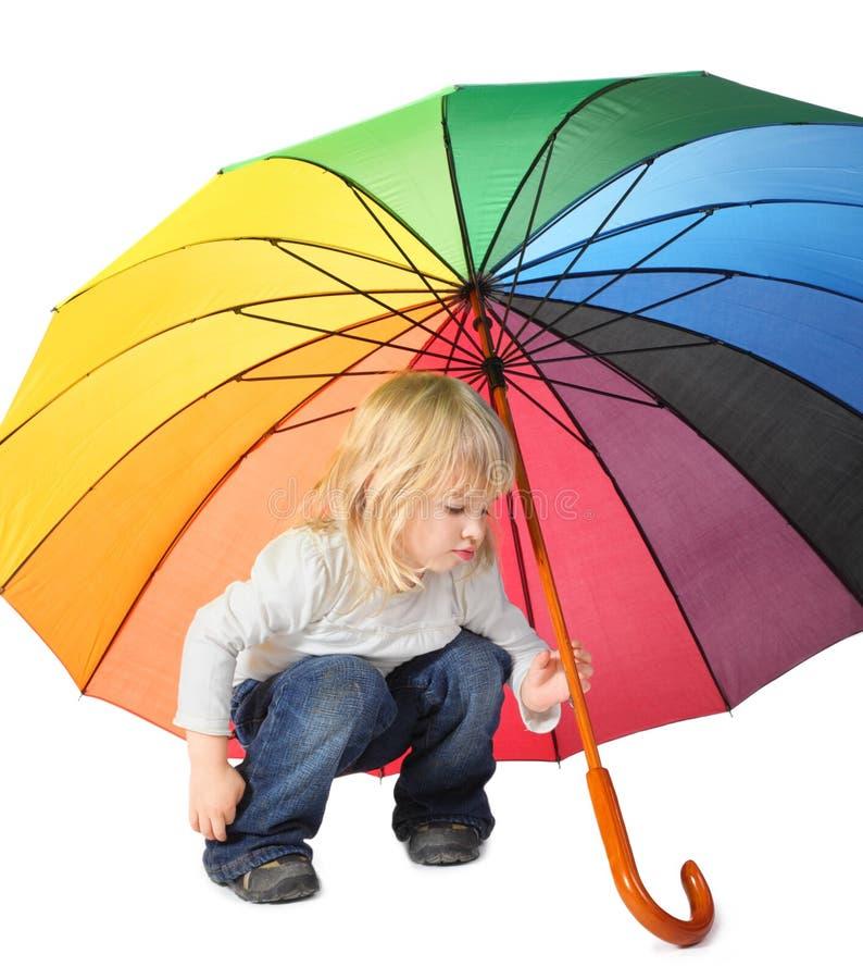 Niña bajo un paraguas coloreado fotografía de archivo