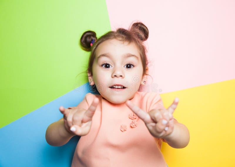 Niña bastante de cuatro años con la cara divertida en fondo multicolor Colores brillantes y imagen elegante imagenes de archivo
