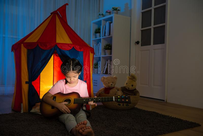 Niña bastante dulce que sostiene la pequeña guitarra fotos de archivo