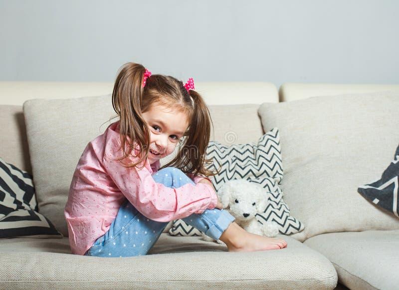 Niña bastante feliz en sentarse que lleva casual en el sofá con el perro de juguete y la sonrisa imagen de archivo libre de regalías
