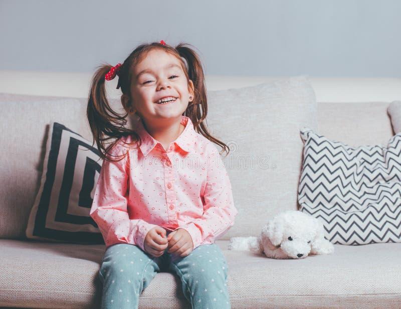 Niña bastante feliz en sentarse que lleva casual en el sofá con el perro de juguete y la sonrisa fotos de archivo