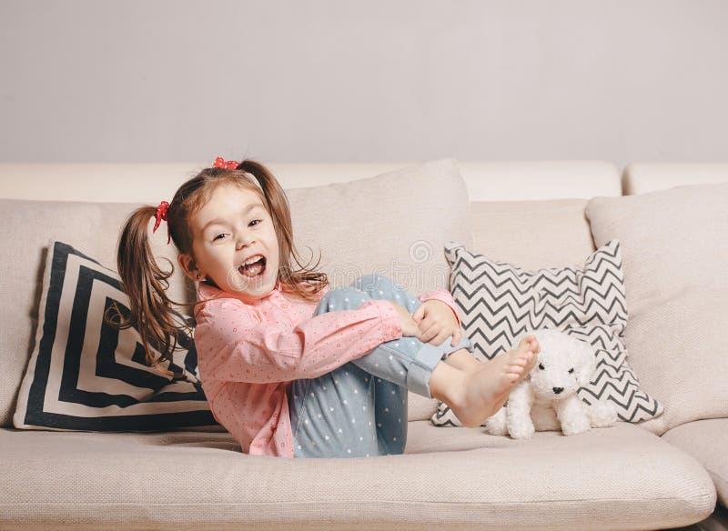 Niña bastante feliz en sentarse que lleva casual en el sofá con el perro de juguete y la sonrisa imagenes de archivo