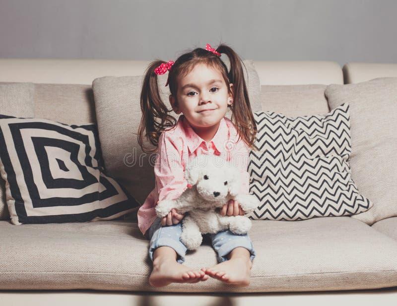 Niña bastante feliz en sentarse que lleva casual en el sofá con el perro de juguete y la sonrisa imágenes de archivo libres de regalías