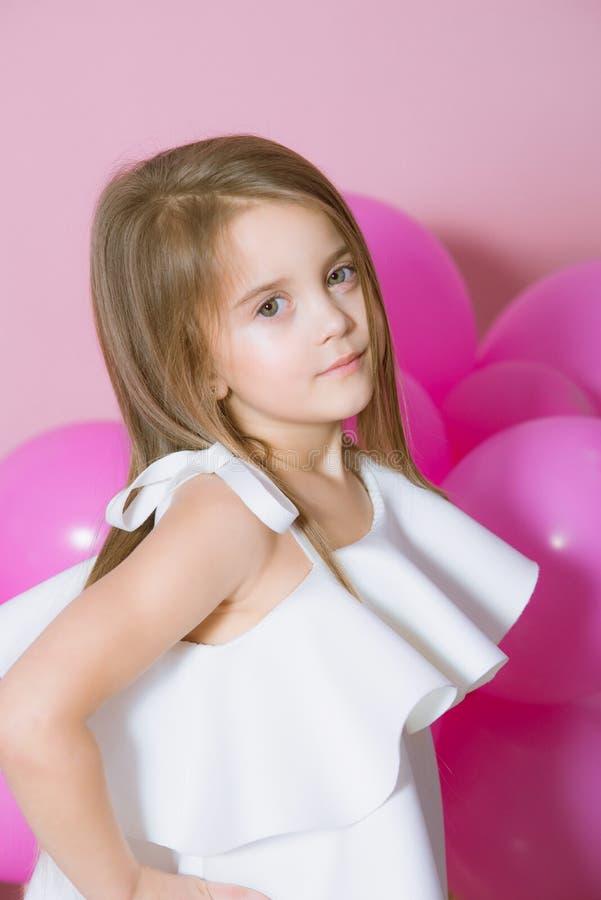 Niña bonita con el pelo rubio hermoso en el vestido blanco que fascina con los globos rosados sobre fondo rosado imagenes de archivo