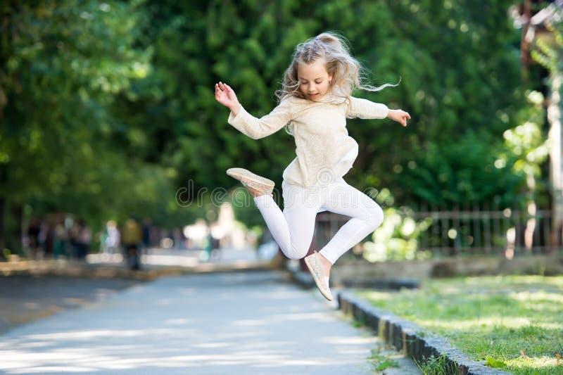 Niña bonita con el pelo rubio rizado que salta en la calle fotos de archivo libres de regalías