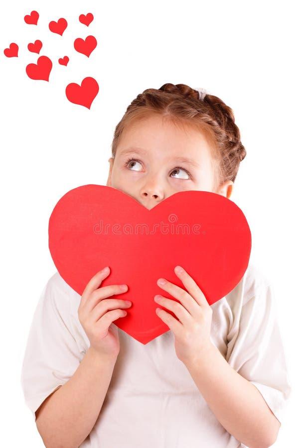 Niña bonita con un corazón rojo grande para el día de tarjeta del día de San Valentín fotos de archivo libres de regalías