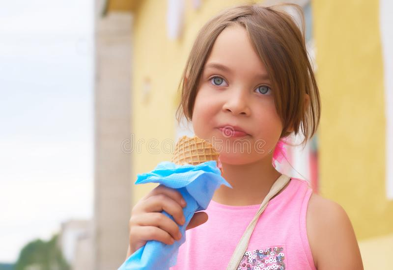 Niña bonita que come lamiendo el helado grande en la risa feliz del cono de las galletas en fondo de la naturaleza fotos de archivo libres de regalías