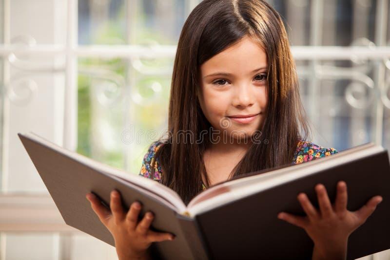Niña bonita que lee una historia fotografía de archivo