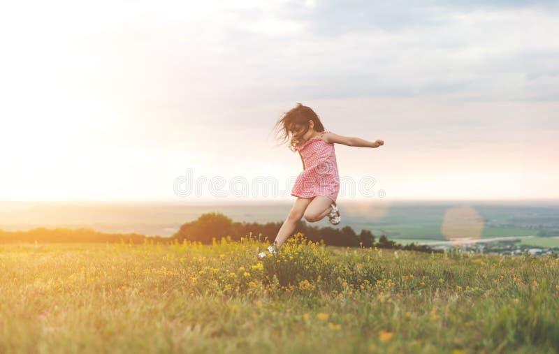 Niña bonita que salta al aire libre imagen de archivo