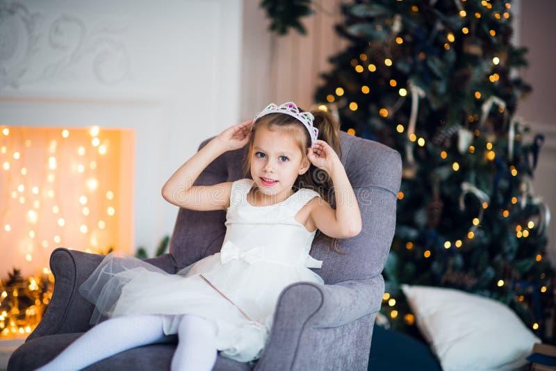 Niña bonita que se sienta en la butaca Atmósfera mágica y festiva imagen de archivo libre de regalías