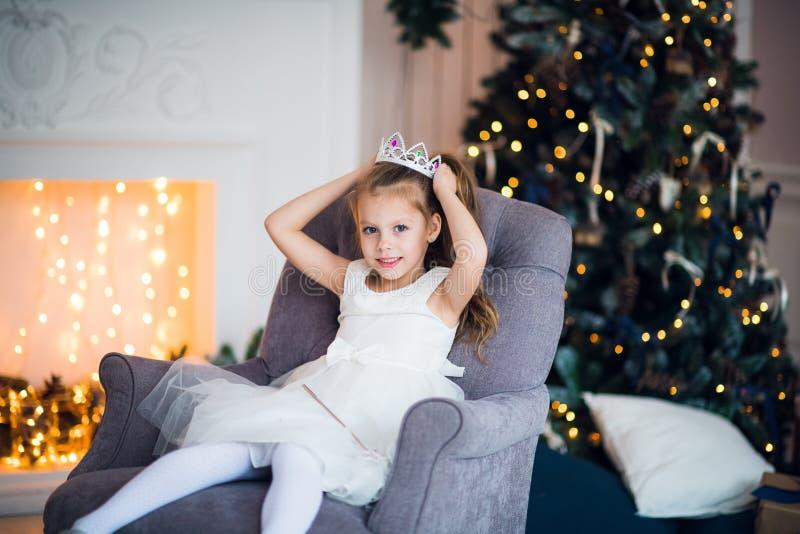 Niña bonita que se sienta en la butaca Atmósfera mágica y festiva fotografía de archivo libre de regalías