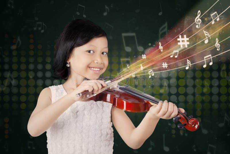 Niña bonita que toca el violín foto de archivo libre de regalías