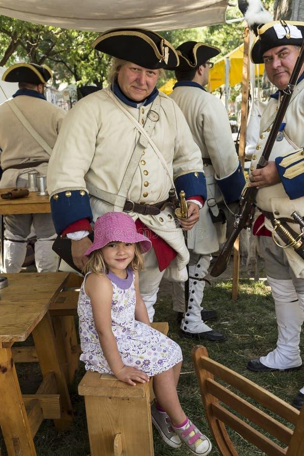 Niña bonita rodeada por los hombres que se colocan vestidos como soldados franceses del siglo XVIII imagen de archivo