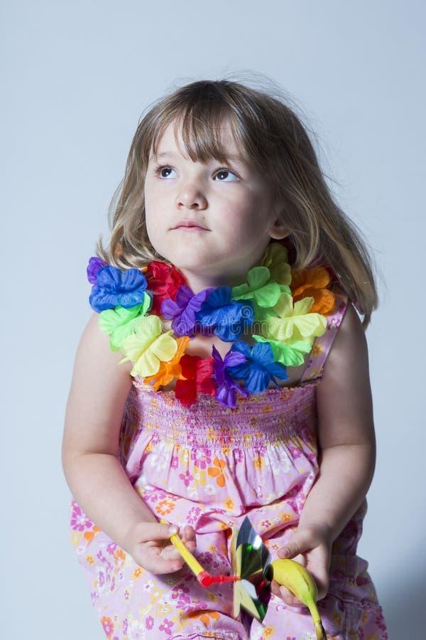 Niña bonita vestida en la guirnalda rosada del vestido de flores y de seda de la flor que se sienta en taburete imagen de archivo