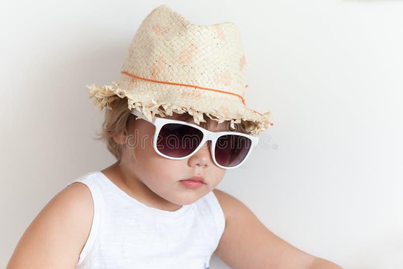 Niña caucásica linda en sombrero de paja y gafas de sol imagenes de archivo