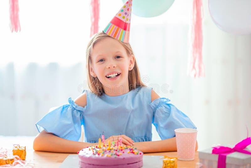 Niña caucásica sonríe soñadoramente y mira la tarta arcoíris de cumpleaños Fondo festivo y colorido con globos imagen de archivo