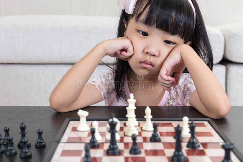Niña china asiática cansada que juega a ajedrez en casa fotografía de archivo libre de regalías