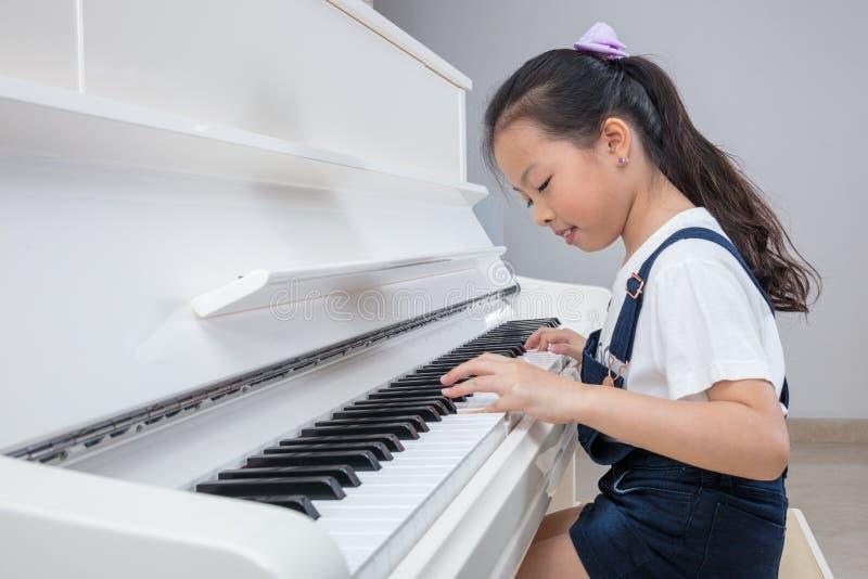 Niña china asiática feliz que juega el piano clásico en casa fotografía de archivo