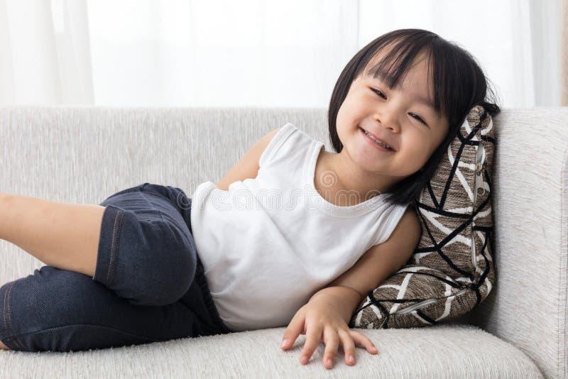 Niña china asiática feliz que se acuesta en el sofá imagenes de archivo