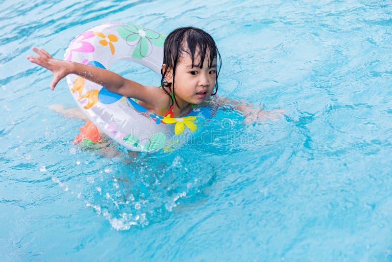 Niña china asiática que aprende nadar en la piscina fotografía de archivo libre de regalías
