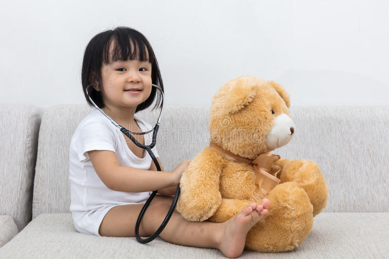 Niña china asiática que comprueba encima de un oso de peluche fotos de archivo