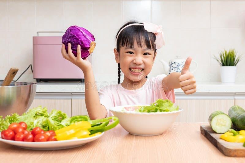 Niña china asiática que hace la ensalada en la cocina imagenes de archivo