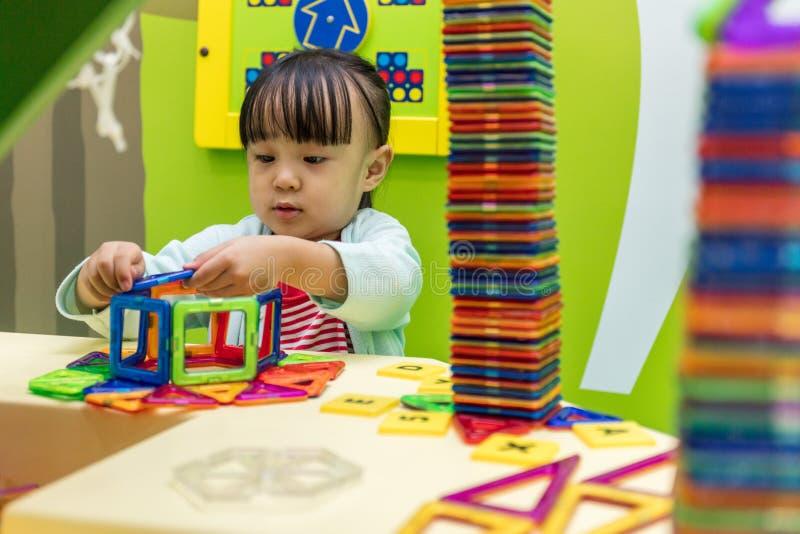 Niña china asiática que juega bloques coloridos del plástico del imán imagen de archivo