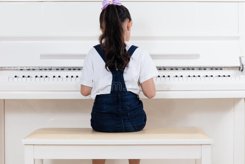 Niña china asiática que juega el piano clásico en casa fotografía de archivo libre de regalías