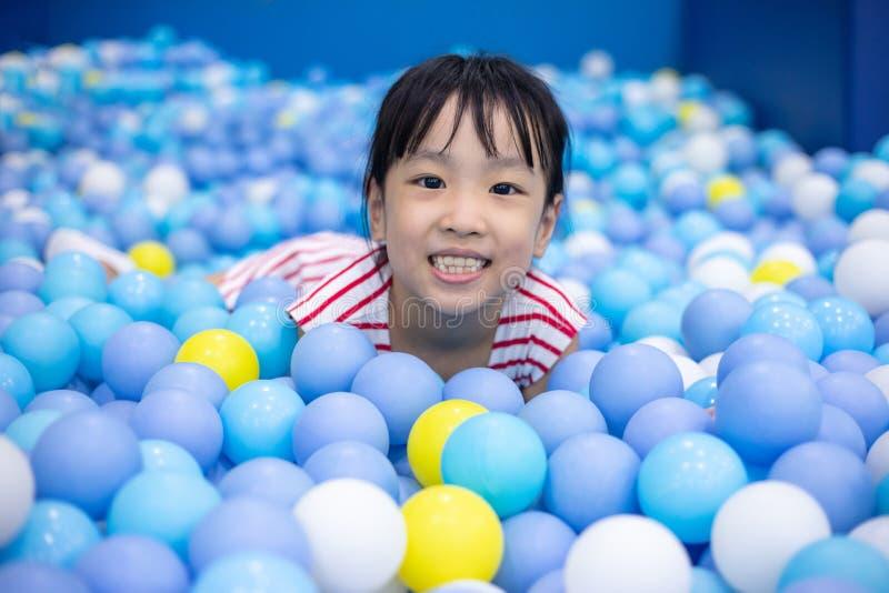 Niña china asiática que juega en la piscina de las bolas imagenes de archivo
