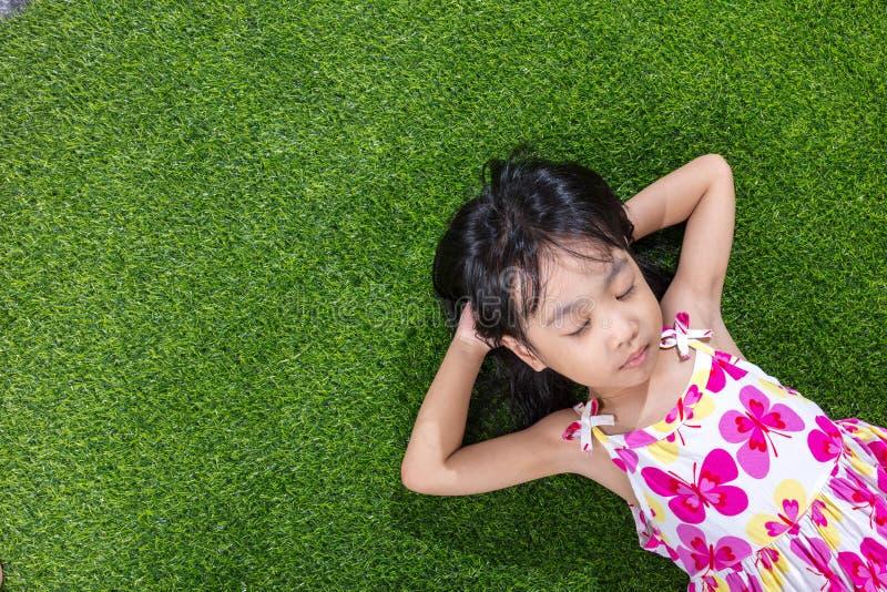 Niña china asiática que miente en la hierba foto de archivo libre de regalías