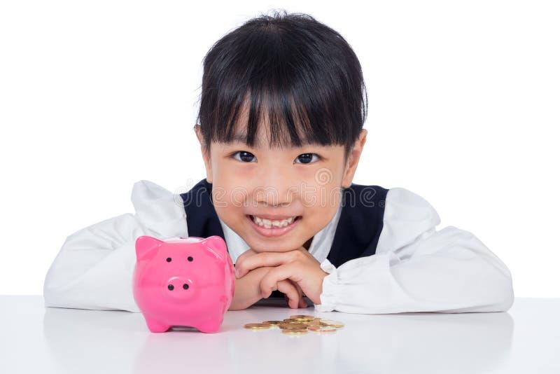 Niña china asiática que sonríe con la hucha fotografía de archivo