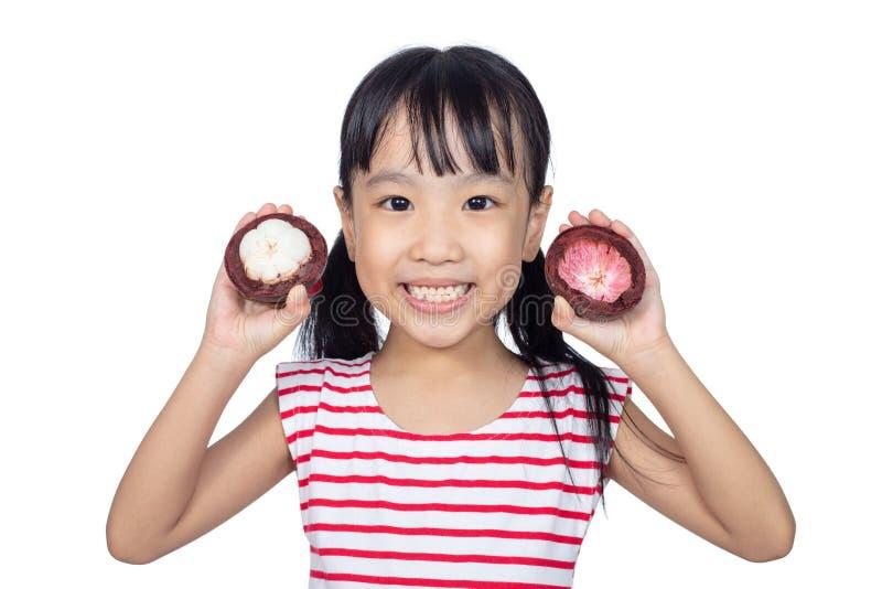 Niña china asiática que sostiene la fruta del mangostán foto de archivo