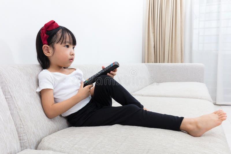 Niña china asiática que sostiene una TV teledirigida foto de archivo