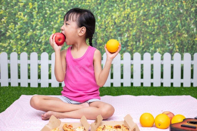 Niña china asiática que tiene comida campestre fotografía de archivo