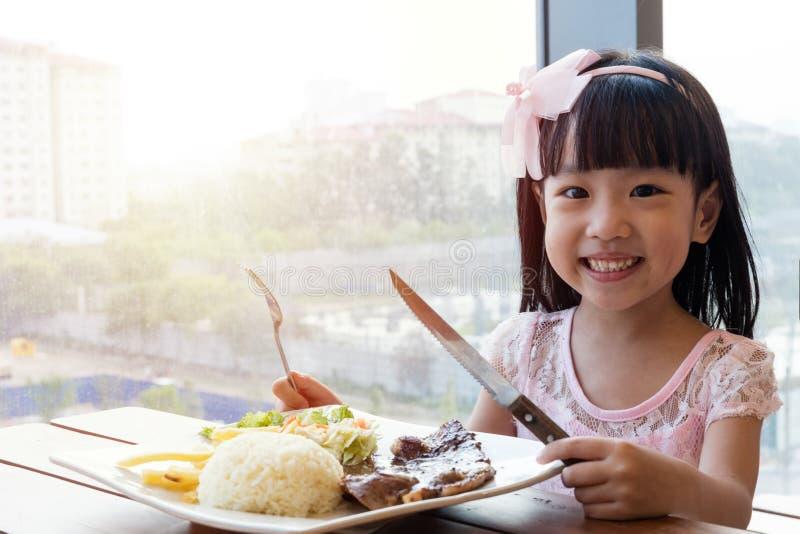 Niña china asiática sonriente que come el filete del cordero con arroz imagen de archivo
