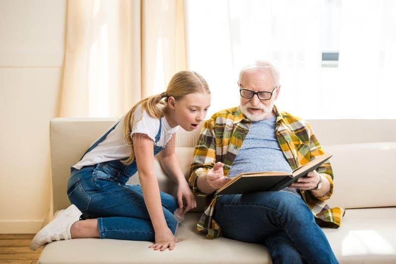 Niña con el abuelo en las lentes que se sientan en el sofá y el libro de lectura foto de archivo