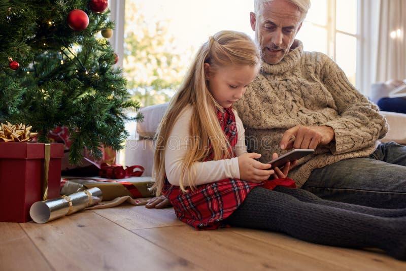 Niña con el abuelo que se sienta el árbol de navidad y usando foto de archivo libre de regalías