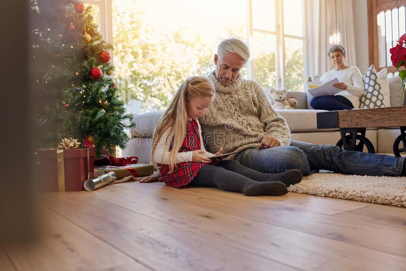 Niña con el abuelo que usa la tableta digital en casa durante fotos de archivo libres de regalías