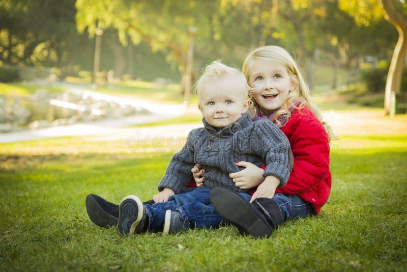 Niña con el bebé Brother Wearing Coats en el parque fotos de archivo